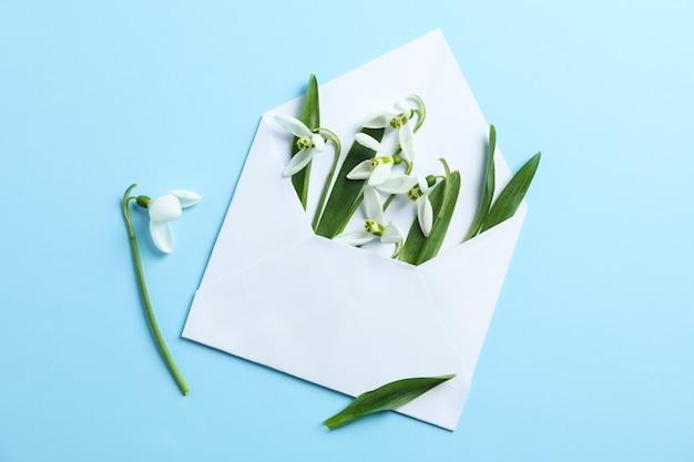 色の背景、テキスト用のスペースにスノードロップの花と封筒