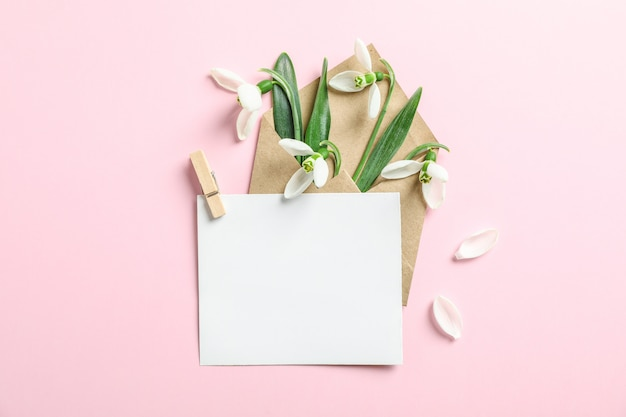 Envelope with snowdrop flowers and paper on color background