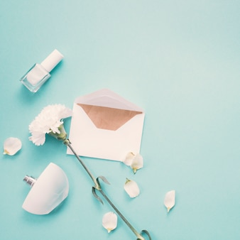 Envelope with white flower and perfume on blue table