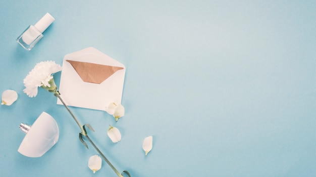 Envelope with white flower and perfume on table