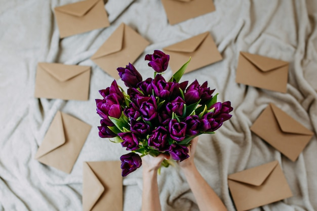 Envelopes of craft paper on beige plaid, spring flowers, bunch of purple tulips with envelopes, woman holds bunch of purple tulips.