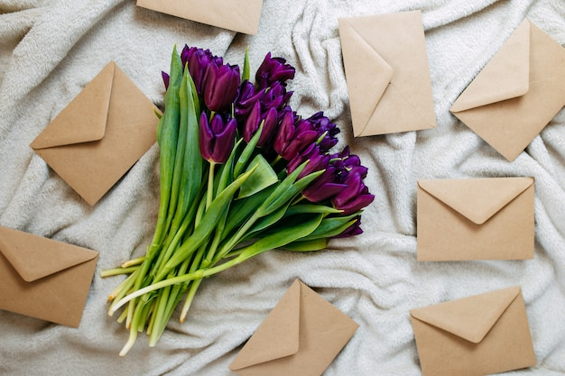 Envelopes of craft paper on beige plaid, spring flowers, bunch of purple tulips with envelopes.