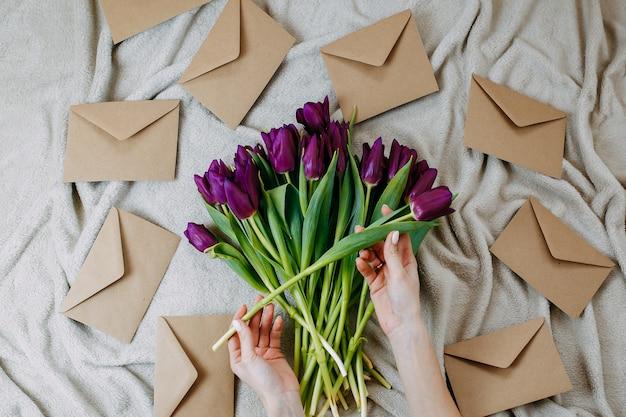 Конверты из крафт-бумаги на бежевом пледе, весенние цветы, букет фиолетовых тюльпанов с конвертами, женщина держит букет фиолетовых тюльпанов.