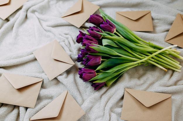 Конверты из крафт-бумаги на бежевом пледе, весенние цветы, букет фиолетовых тюльпанов с конвертами.