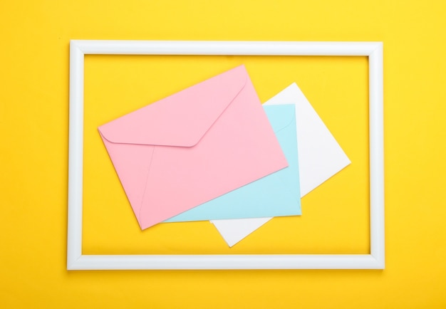 Envelopes in a white frame on a yellow surface