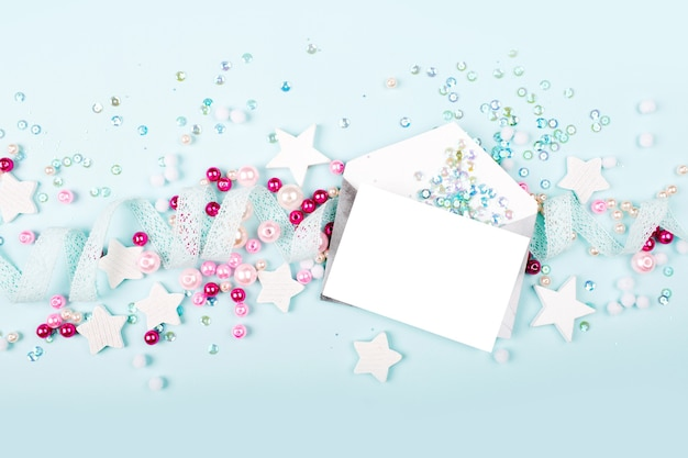 Envelopes with empty card on blue background with  with cute decoration: heart, lace ribbon, stars and sequins. flat lay, top view