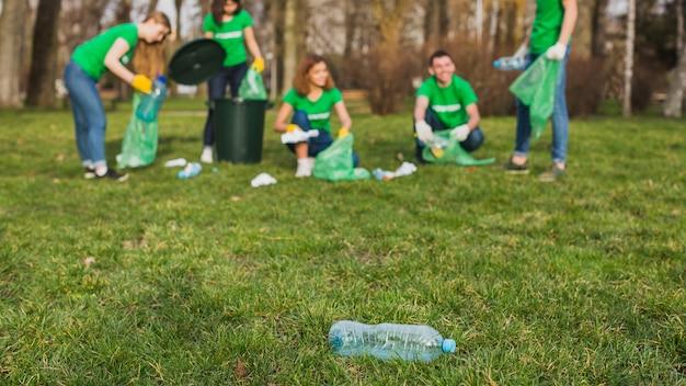 Окружающая среда и концепция добровольца с бутылкой на траве