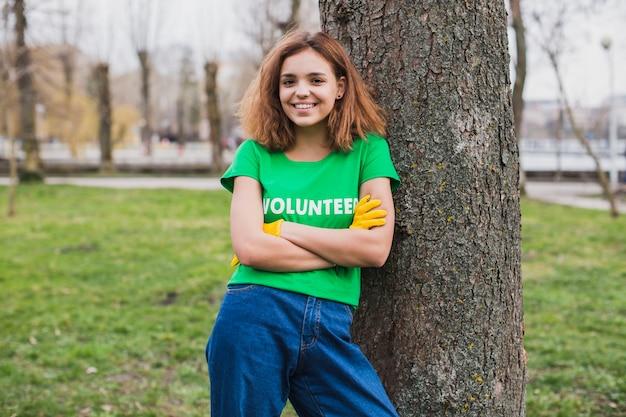Окружающая среда и концепция добровольца с женщиной, прислонившись к дереву