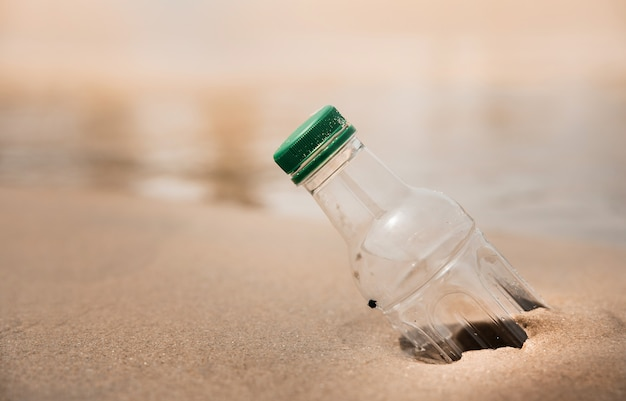 Environment, ecology care, renewable concept. plastic bottle waste on the beach sand or riverside
