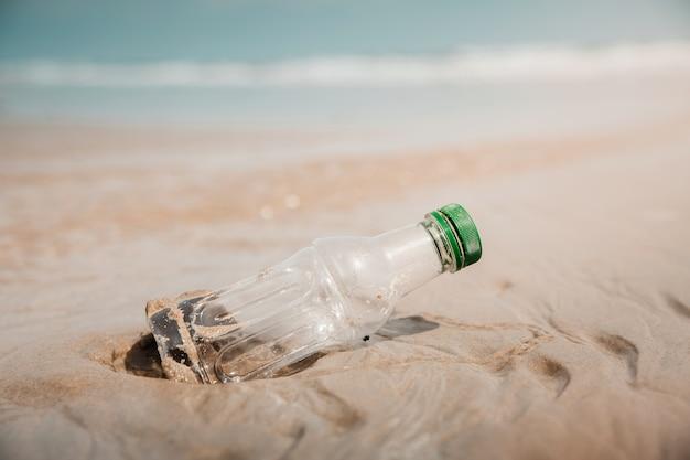 環境、エコロジーケア、再生可能コンセプト。ビーチの砂のペットボトル廃棄物