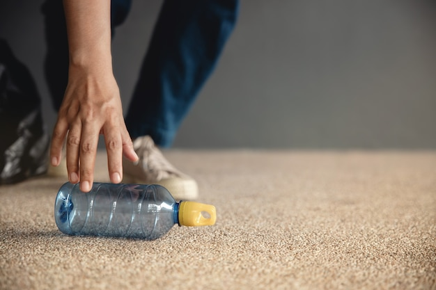 環境エコロジーケア再生可能コンセプトボランティアが床にペットボトルの廃棄物を収集