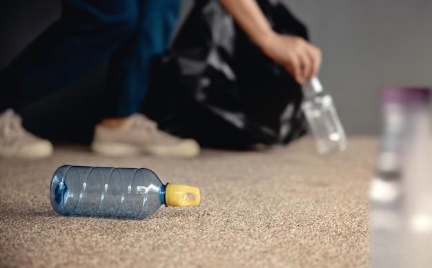 環境、エコロジーケア、再生可能コンセプト。公共の床でペットボトルの廃棄物を収集してゴミ箱に捨てるボランティア。都市を清潔に保つ。クローズアップとセレクティブフォーカス