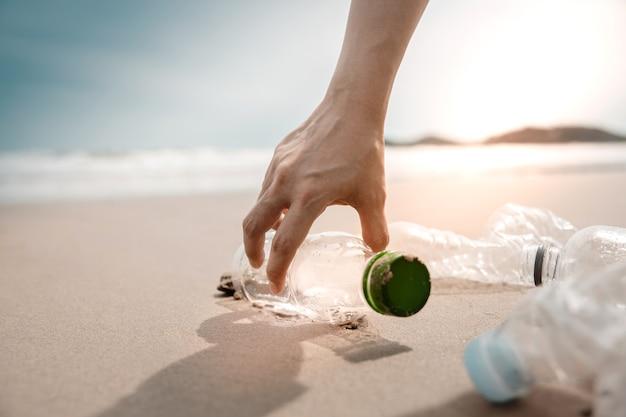 環境、エコロジーケア。ビーチの砂でペットボトルの廃棄物を収集するボランティアまたは旅行者