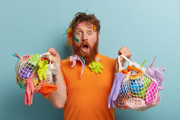 Environment protection concept. puzzled shocked redhead bearded man stares, astonished by nature disaster, collects plastic rubbish, models over blue wall with two bags of garbage