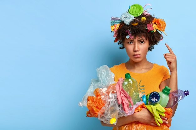 Environment protection and volunteering concept. displeased afro woman points at head with plastic waste