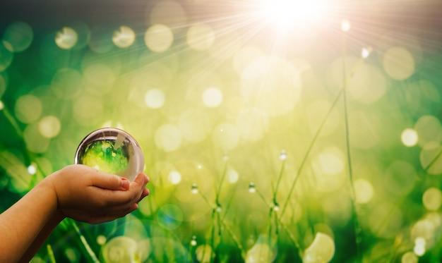 환경은 깨끗한 행성 생태 개념을 저장합니다. 수정 지구 지구본을 들고 있는 어린이 손