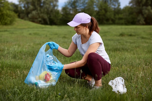 Environmental activist picking up trash on green meadow, calls for reusing and recycling things