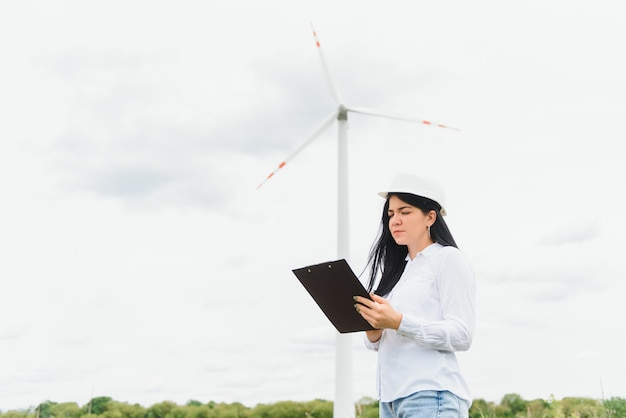 Инженер-эколог с ноутбуком на ветряной электростанции