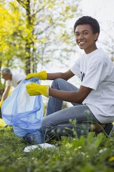 Экологическая работа. веселый самец-волонтер улыбается в камеру и собирает мусор