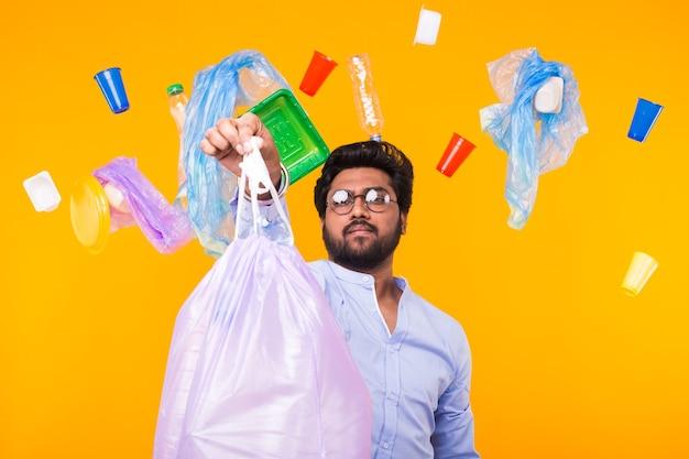 環境汚染、プラスチックのリサイクル問題、エコロジー問題の概念-黄色い壁にゴミ袋を持っている悲しいインド人。