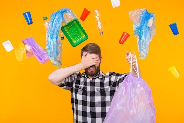 環境汚染、プラスチックのリサイクル問題、エコロジー問題の概念-ゴミ袋を持って黄色い壁に手のひらで目を覆っている悲しい男。