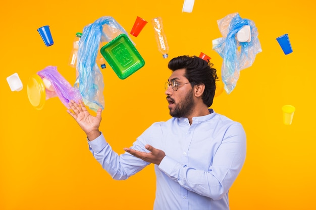 Загрязнение окружающей среды, проблема переработки пластика и концепция утилизации отходов - удивленный индеец на желтом фоне с мусором.