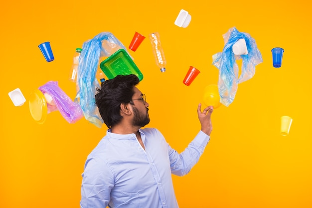 Environmental pollution, plastic recycling problem and waste disposal concept - surprised indian man holding garbage bag