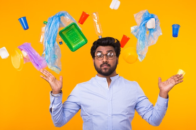 Environmental pollution, plastic recycling problem and waste disposal concept - surprised indian man threw up his arms to the sides on yellow background with trash