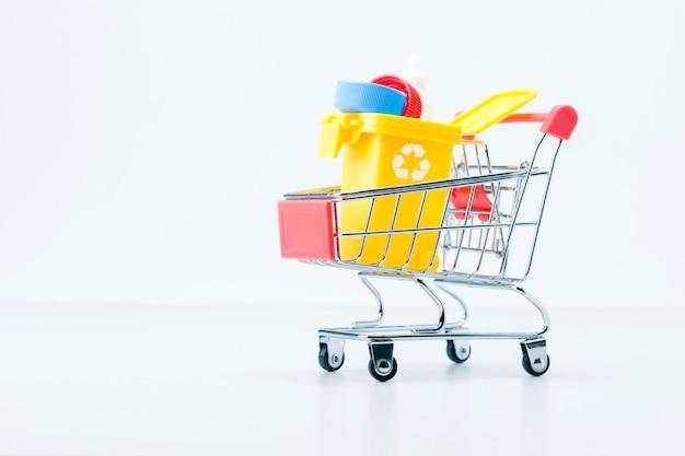 環境、汚染プラスチックごみの概念。ショッピングカートにゴミが入ったモダンなゴミ箱。