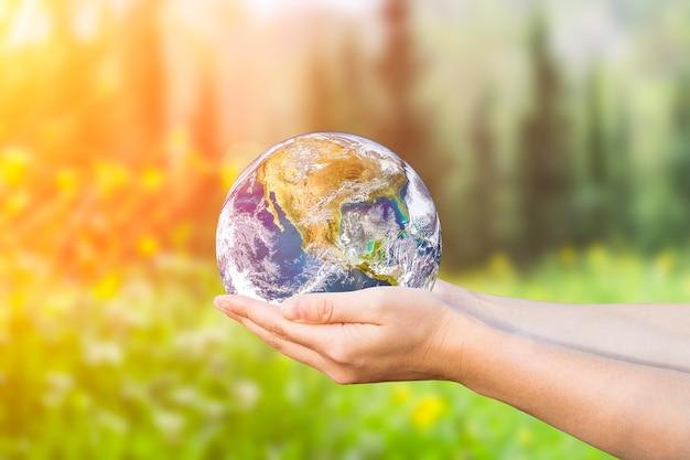 배경에 여성의 손에 환경 보호 및 자연 보전 개념 행성 지구...