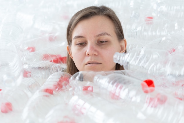 Environmental protection, people and recyclable plastic concept - exhausted woman concerned