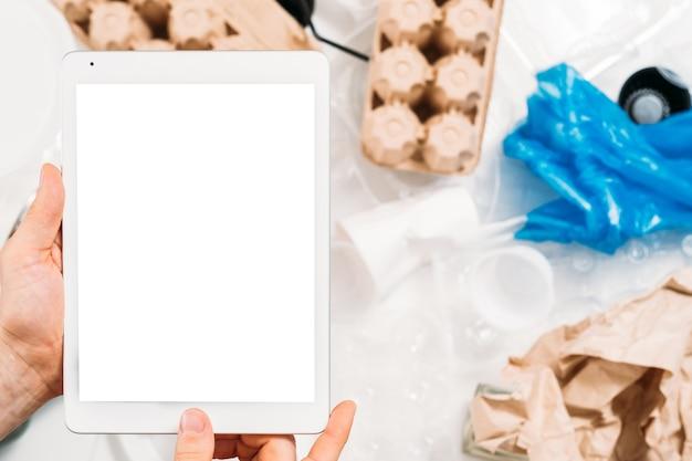 Защита окружающей среды. мотивация в социальных сетях. крупный план планшета экрана макета в руках человека над засорением мусора.