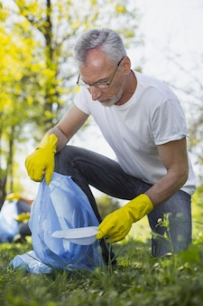 Экологическая задача. низкий угол красивого зрелого добровольца в очках и сбор мусора