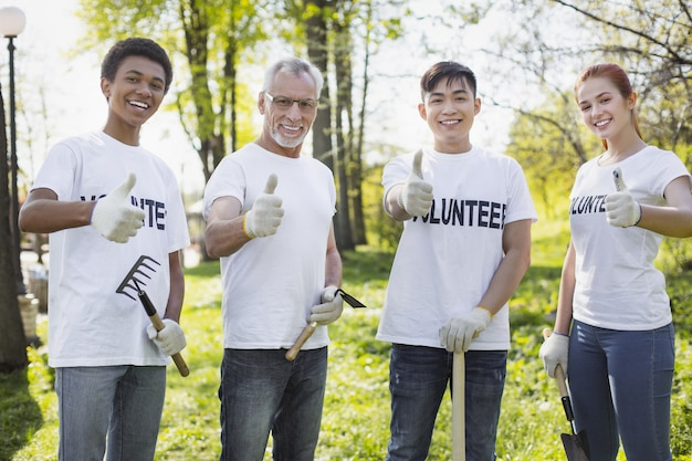 Environmental volunteering option. merry four volunteers showing thumbs and holding garden tools
