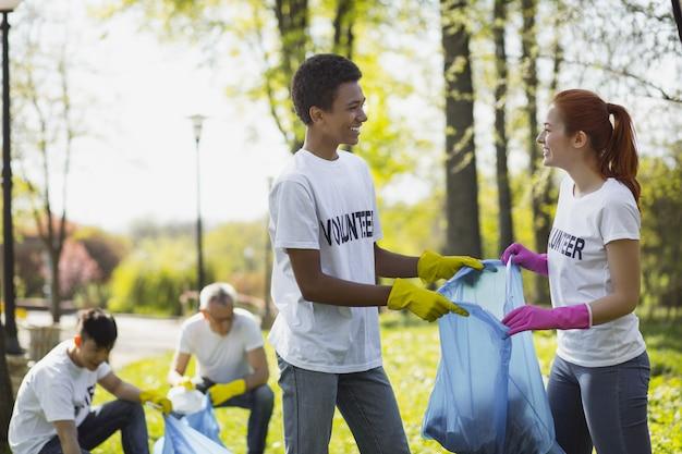 Экологическое волонтерство. позитивные два добровольца держат мешок для мусора и смотрят друг на друга