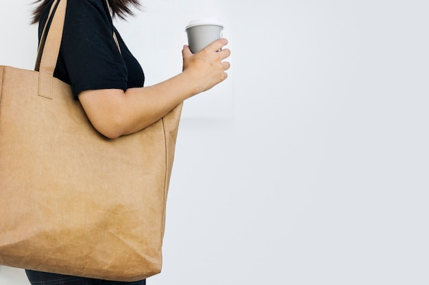 デザインスペースで環境にやさしいトートバッグの写真を使用している環境保護主義者の女性