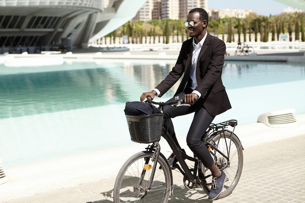 Environmentally friendly afro american banker in formal wear and shades looking happy and relaxed, cycling to work on bike in urban setting, smiling cheerfully. businesspeople, lifestyle and transport
