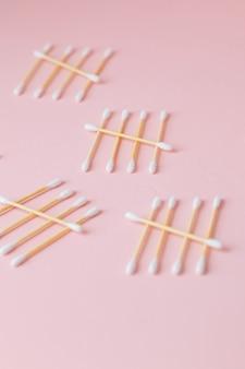 ピンクの背景の竹の歯ブラシの環境に優しい竹と綿棒のつぼみ