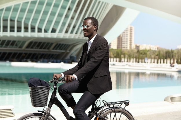 Environmentally friendly black manager in formal suit and sunglasses looking forward while riding bicycle to work in urban surroundings, smiling happily. business, lifestyle, transport and people