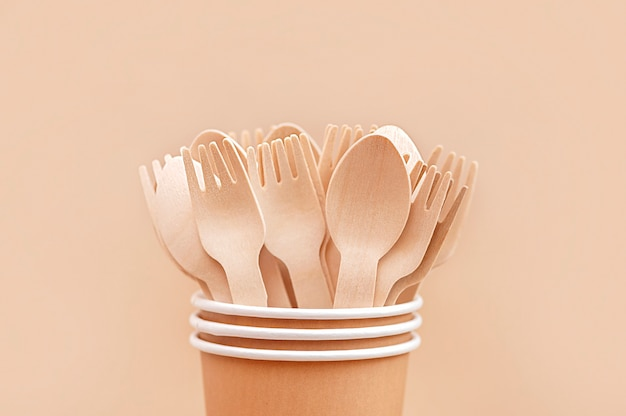 Environmentally friendly disposable tableware wooden spoons and forks in paper cups close up
