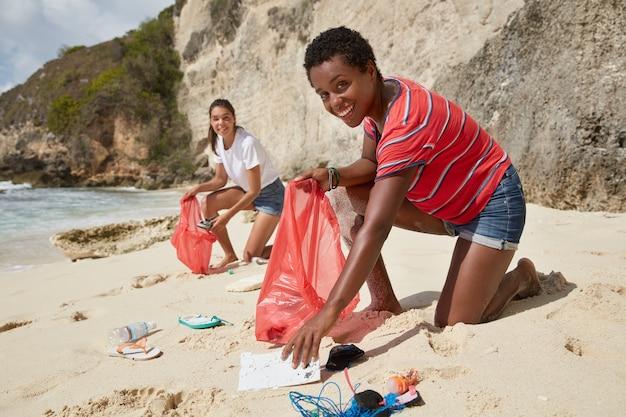 Экологически чистые многонациональные женщины собирают на берегу моря пластмассовые и резиновые изделия.