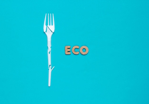 Environmentally friendly still life. broken plastic fork on a blue background with the word eco.