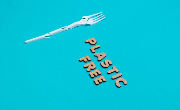 Environmentally friendly still life. broken plastic fork on blue background with the word eco.