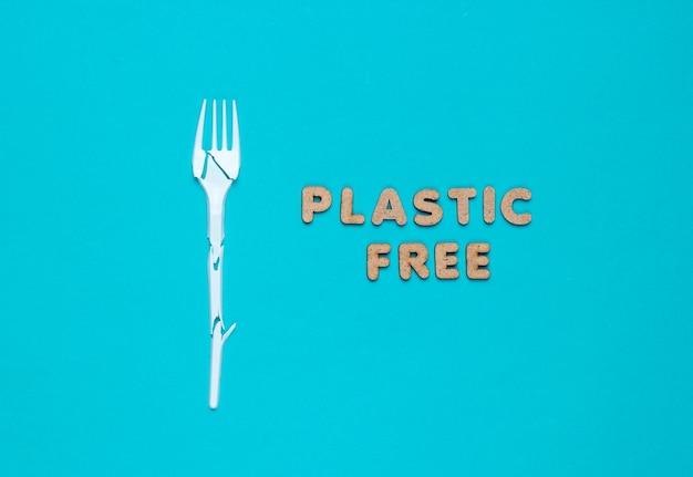 環境にやさしい静物。エコという言葉で青い背景に壊れたプラスチックフォーク。