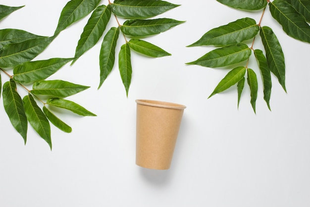 Environmentally friendly still life. disposable craft cardboard coffee cup on a white background with green tropical leaves. dishes with natural materials
