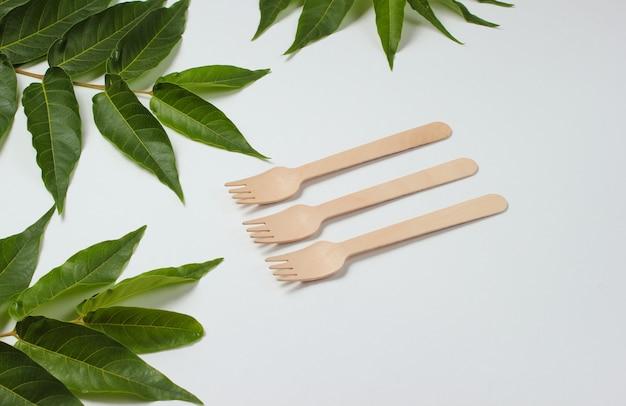 환경 친화적 인 정물. 녹색 열 대 잎과 흰색 배경에 일회용 나무 포크. 천연 재료로 만든 칼 붙이