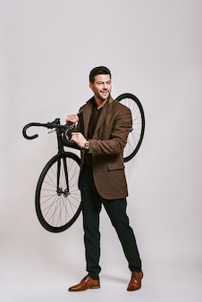 Environmentally friendly stylish darkhaired man holding bicycle in his hands smiling and looking