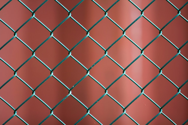 孤立した塗装シンプルな幾何学的な黒鉄金属ワイヤチェーンリンクフェンスeon濃い赤の背景のクローズアップ。フェンス、保護、エンクロージャーのコンセプト。