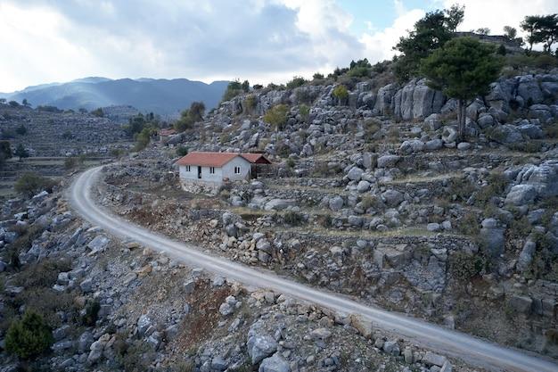 壮大な山の谷の風景。ロッキー山脈の間の曲がりくねった道。山の斜面に赤い屋根の家。トルコ、ヨーロッパ。