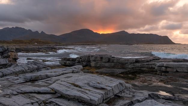ノルウェーの北海と険しい崖に沈む夕日